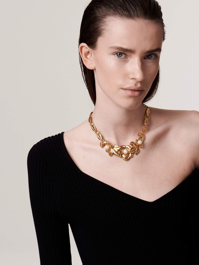 Woman in black dress wearing flower Chanel necklace with pearls