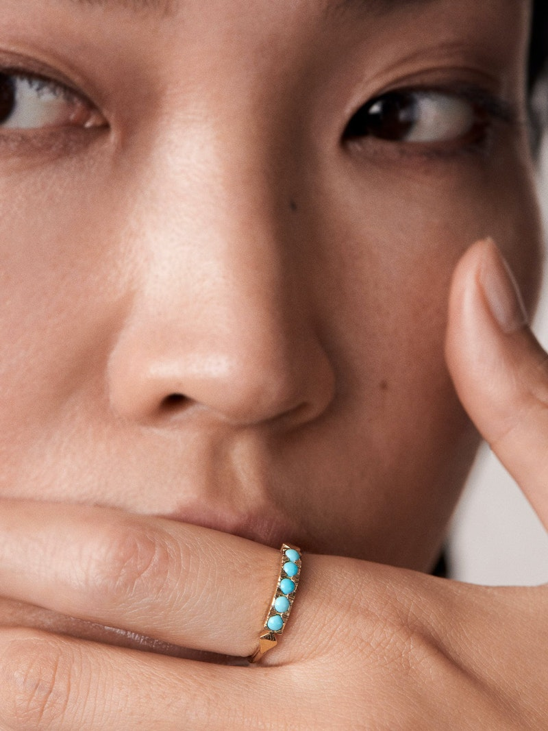 Turquoise triangles on gold ring close to face