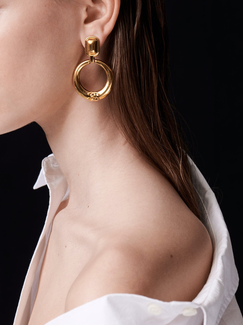 Close-up of woman wearing a white shirt and a gold Chanel earring